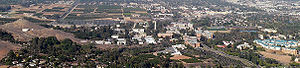 Panoramic view of campus from the Box Springs Mountain. Student housing is to the far lower right, north of which are the athletic facilities. The dense vegetation to the lower left constitutes the Botanic Gardens. The agricultural fields in the central left are designated for future campus development. (2007)