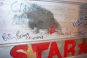 "Woody Guthrie Folk Festival - Billy Bragg signed the wall in the ""green room"" of the Crystal Theater on Woody's birthday in 1998; Ellis Paul on the same date in 2000."