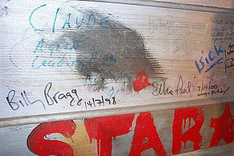 """Woody Guthrie Folk Festival - Billy Bragg signed the wall in the """"green room"""" of the Crystal Theater on Woody's birthday in 1998; Ellis Paul on the same date in 2000."""