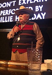 An elderly Caucasian male with a long white mustache. He is wearing a cowboy hat and striped waistcoat while holding a microphone. He is standing in front of a screen.
