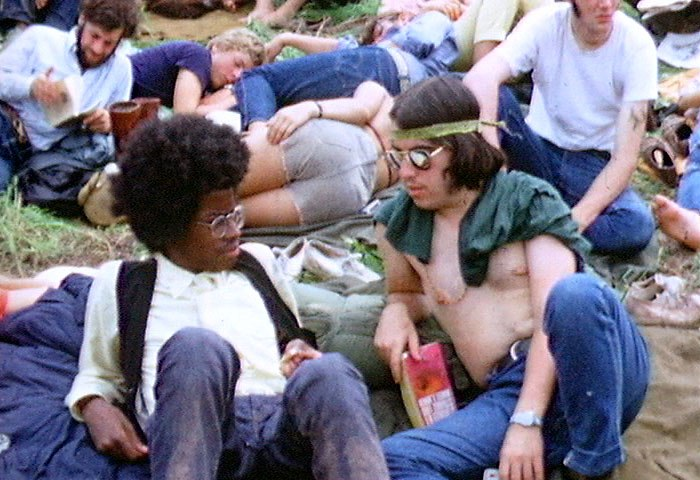 A color photograph showing people from the 1969 Woodstock Festival sitting on grass, in the foreground a back and a white male look at each other