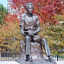 A statue of young Lincoln sitting on a stump, holding a book open on his lap