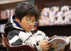 An asian boy reading GRAPHiC N0VEL in a Barnes...