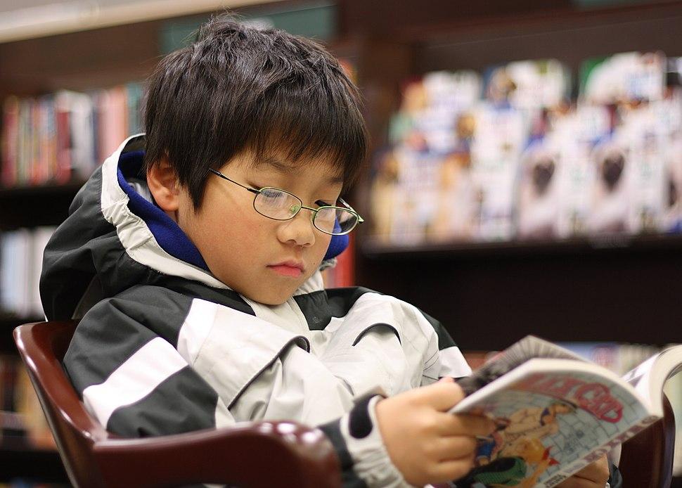 Young boy reading manga