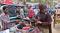 Young girl buys pickles from street vendor.jpg