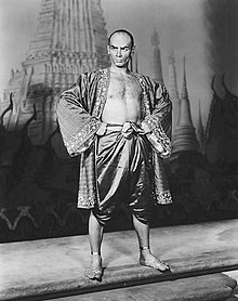 Black and white photo of a man with a shaven head in silky Asian garb; his chest is exposed and his feet are bare; he stands with hands on hips, glowering at the camera