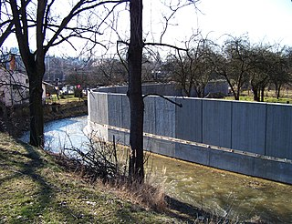 Flood wall mostly vertical artificial barrier to temporarily contain the waters of a waterway which may flood
