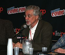 Denis Kitchen, a bespectacled middle-aged man, seated at a Comic Con dais