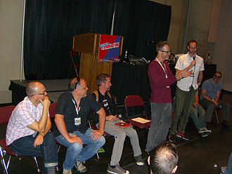Scott Brick - Brick, standing in the red shirt, at the 2012 New York Comic Con.