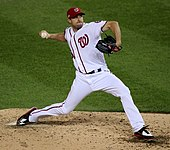 "A man in a white baseball uniform with the Washington Nationals' red ""W"" on the front throws a pitch."