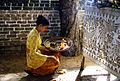 A Hindu woman in prayers with offerings Bali Indonesia.jpg