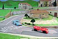 A Magracing Ferrari and Porsche race out of the village on my Targa Florio mountain circuit..JPG