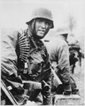 A Nazi soldier, heavily armed, carries ammunition boxes forward with companion in territory taken by their... - NARA - 531230.tif
