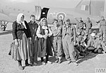 A group of partisan and civilian women stand with other members of the Yugoslav National Liberation Army after arriving at the air evacuation centre at Bari, Italy, on Douglas Dakota Mark III.jpg