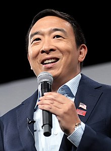 Andrew Yang holding a microphone while making a speech