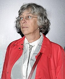 A woman wearing a red jacket, cropped from a group photograph