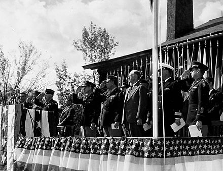 "Presentation of the Army-Navy ""E"" Award at Los Alamos on 16 October 1945. Standing, left to right: J. Robert Oppenheimer, unidentified, unidentified, Kenneth Nichols, Leslie Groves, Robert Gordon Sproul, William Sterling Parsons. Army-Navy E Award Ceremony 68997.jpg"