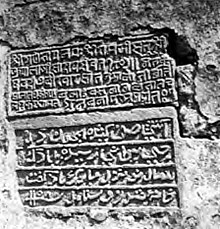 stone carving of text on wall, with 5 lines of Sanskrit then 4 lines of Persian looking like Arabic script
