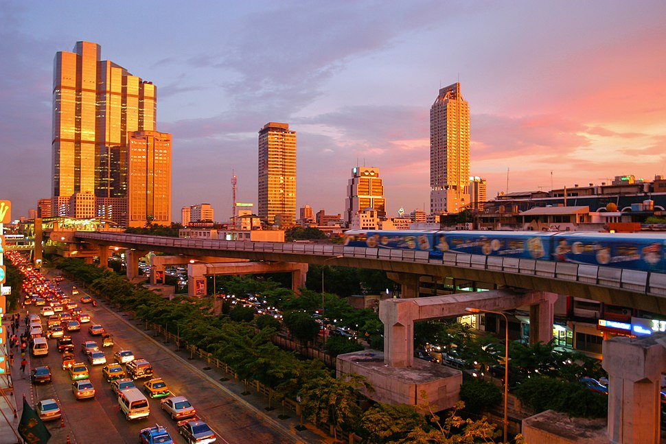 A road with a lot of traffic; an elevated train running above the road; several buildings, one with the appearance of a robot, during sunset