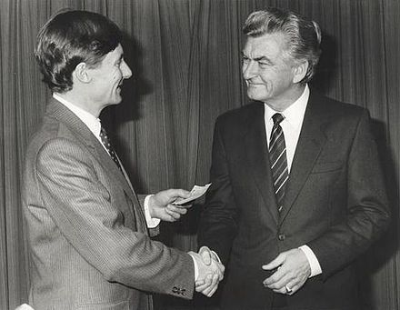 Hawke presenting a relief cheque to John Bannon, Premier of South Australia, in April 1983, in the aftermath of the Ash Wednesday bushfires. BannonHawke.jpg