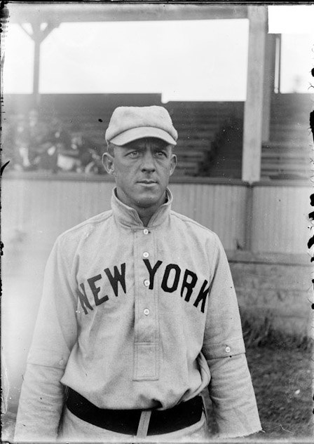 Baseball player, Billy Gilbert, New York Giants, standing on a baseball field near the grandstand