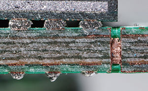 Printed circuit board - Cut through a SDRAM-module, a multi-layer PCB. Note the via, visible as a bright copper-colored band running between the top and bottom layers of the board.