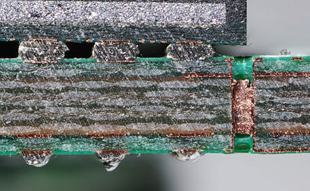 Cut through a SDRAM-module, a multi-layer PCB. Note the via, visible as a bright copper-colored band running between the top and bottom layers of the board. Bga und via IMGP4531 wp.jpg