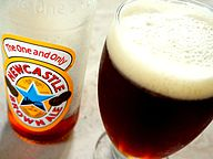 "A wide Geordie schooner glass with a stem, filled with dark brown beer with a large foam head. Next to it is a mostly-empty bottle labelled ""The One and Only: Newcastle Brown Ale"""