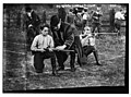Boy Scouts learning to shoot. Two boys kneeling on ground with the instuctor between. LCCN2014688125.jpg