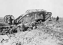 Early World War I tank, with soldiers in a trench next to it