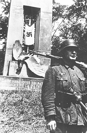 "Armistice of 22 June 1940 - Shortly before its destruction, the 1918 ""Alsace-Lorraine monument"", depicting a German eagle impaled by a sword, now covered with the Third Reich flag, and guarded by a German soldier."