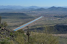picture of a straight blue ribbon of water, the canal, running through the desert, from a vantage point of one of the mountains surrounding the city.