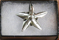 A five-pointed star pin made of fountain pen nibs resting in a small box