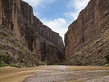 A brown river between two towering canyon walls