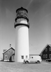 "High-resolution black and white photo of the lighthouse and keeper's house.  Parked in front of the lighthouse is a 1950s van, with a military emblem and the words ""United States Coast Guard"" stenciled on the driver's door, and on the side of the van is a military advertisement that reads ""The U.S. Coast Guard NEEDS MEN! Join Now! No waiting""."