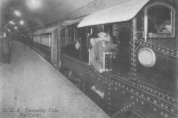 a large electric locomotive sits at a dimly lit platform underground with carriages behind. The cap-wearing driver and his assistant pose for the camera at the controls. Other staff are visible along the platform.