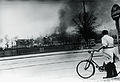 Cyclist looking at the burning Shellhouse (Getapos head quarter) after the RAF attack.. 18th April 1944. (9443121064).jpg