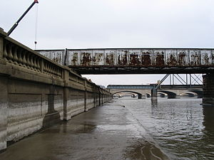 Des Moines River - The Des Moines River, as it flows through downtown Des Moines, west bank, during spring high water; note the old watermarks on the flood wall.