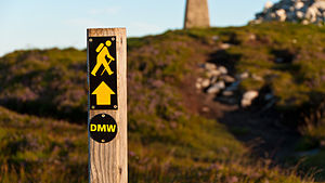 "Dublin Mountains Way - Waymarker on the Dublin Mountains Way at Fairy Castle with yellow man symbol and ""DMW"" sign"