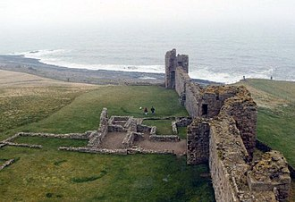 Dunstanburgh Castle - The remains of the Constable's house and complex of buildings (left) and the Constable's Tower (right)