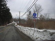 A rural, narrow two-lane highway passes through an area composed of trees, fields, and small brush. There is a snow berm at the side, and a pentagonal orange-on-blue sign with the number 81 at right.