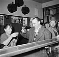 Een van de mannen proost met een vrouw aan de bar van een café, Bestanddeelnr 252-9495.jpg