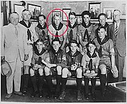Two men in suits and another man in a boy scout uniform stand beside 10 seated teenaged boys in Boy Scout uniforms. Ford is indicated by a red circle.