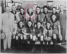 Dois homens em ternos e outro homem em uma posição uniforme escoteiro ao lado de 10 adolescente meninos sentados em uniformes de escoteiro.  Ford está indicado por um círculo vermelho.