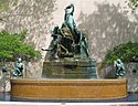 An outdoor fountain with water passing from one plate two another until it ends up in the fountain base. The fountain has several women holding plates and is backed by a structural wall. Trees are adjacent to the fountain on either side.
