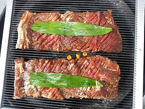 Galbi - Grilling yangnyeom-galbi (marinated short-ribs) with bamboo leaves on a gridiron