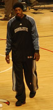 A man, wearing black pants and a black shirt with the word «CHARLOTTE» on the front, is walking on a basketball court.