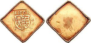 Zwei quadratische auf einer Ecke stehende Goldmünzen nebeneinander, die linke zeigt ein Wappen mit zwei Schwertern und darüber die Buchstaben H HF G K, die rechte Münze ist ohne Schrift oder Bilder