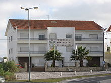 "Headquarters of the Portuguese Badminton Federation. Three-story white building with balconies. Logo and ""Federação Portuguesa de Badminton"" written on tiles on façade."