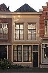 foto van Pand met eenvoudige gepleisterde lijstgevel voor pand van parterre en verdieping